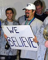 "Troy Dayak holds up the ""We Believe"" sign that became the team's motto during the 2003 MLS playoffs as Brian Mullan (left) and Josh Saunders (right) look on during the lockerroom postgame celebration.  The San Jose Earthquakes defeated the Chicago Fire 4-2 in the MLS Championship at The Home Depot Center on November 23, 2003."