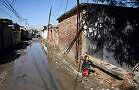 A child plays on a small road in a migrant worker village on the outskirts of Beijing.