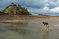 Boy playing in the sea at the water's edge, Anse du Guesclin, Brittany, France.