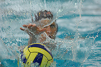 A waterpolo player reaches out to get the ball.