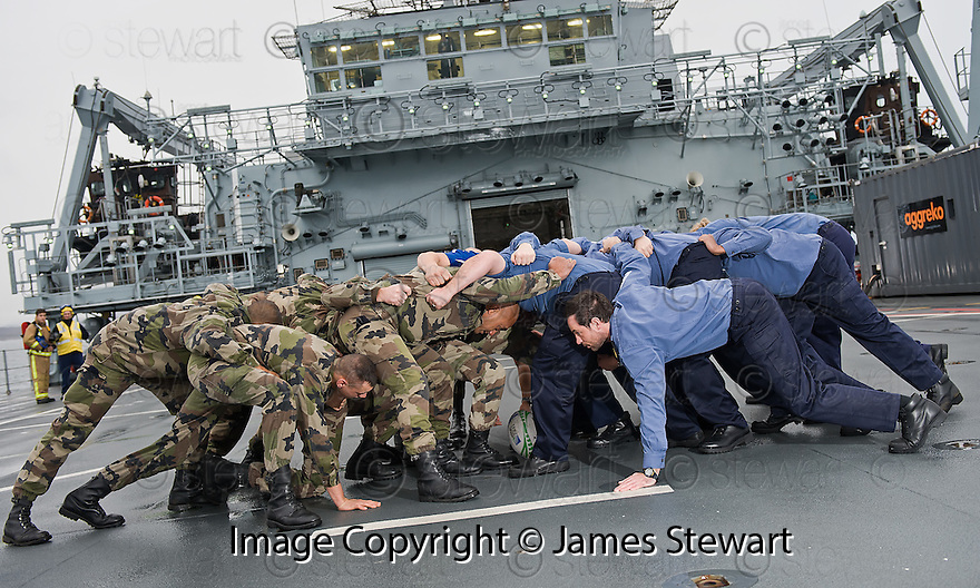 MEMBERS OF THE FRENCH MARINES AND THE ROYAL NAVY FORM A SCRUM ON THE FLIGHT DECK OF HMS BULWARK AHEAD OF WATCHING THE RUGBY WORLD CUP QUARTER FINAL BETWEEN THEIR TWO COUNTRIES WHILST ON A BREAK FROM A JOINT EXERCISE IN LOCH EWE AND OFF THE SCOTTISH ATLANTIC COAST