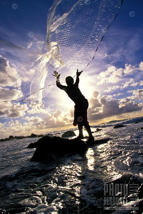 Young local Hawaiian man net fishing of the Kona Coast on the Big Island of Hawaii
