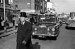 Hoxton funeral east London. Hoxton Street, funeral director in formal top hat walks in front of the heart through Hoxton. 1978.<br /> <br /> My ref 27/3514/,1978,
