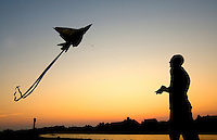 A man is silhouetted as he flies a kite on the beaches of Sullivan's Island, near Charleston, SC. Model release.