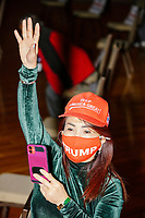A woman wearing a Keep America Great hat waves in the audience before Eric Trump, son of US president Donald Trump, holds a Make America Great Again! campaign rally at the DoubleTree by Hilton Manchester Downtown in Manchester, New Hampshire, on Mon., Oct. 19, 2020. The audience chairs are distanced to follow safety protocols during the ongoing Coronavirus (COVID-19) global pandemic, just a few weeks after Donald Trump himself contracted the disease, though many other Trump campaign events are lax about COVID safety protocols.