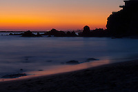 A long-exposure shot taken after sunset at Little Corona beach in Corona Del Mar (Newport Beach), CA.  The rocky line at the horizon is the entrance to Newport Harbor.  There were absolutely no clouds for this sunset, but I love the orange/red hues.