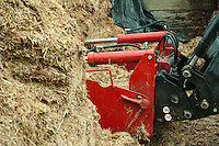 Front-end loader on a tractor with grab at a maize silage face.