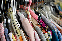 Rack of woman's dresses displayed at a thrift shop.