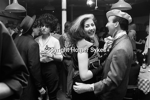 """Blitz Club Covent Garden London 1980. <br /> <br /> Stephen Jones the milliner in beret dancing  with Jayne Chilkes. He is wearing """"... my father's suit, but he certainly didn't wear it with cream gloves, a cream beret and a pussy cat bow.""""<br /> The other couple are Dick Jewell, a film-maker, and his girlfriend, Luciana Martinez.<br /> My ref 9a/3995/1980"""
