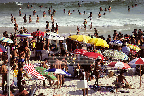 Rio de Janeiro, Brazil. Busy beach with people on the beach and in the sea and sunshades.