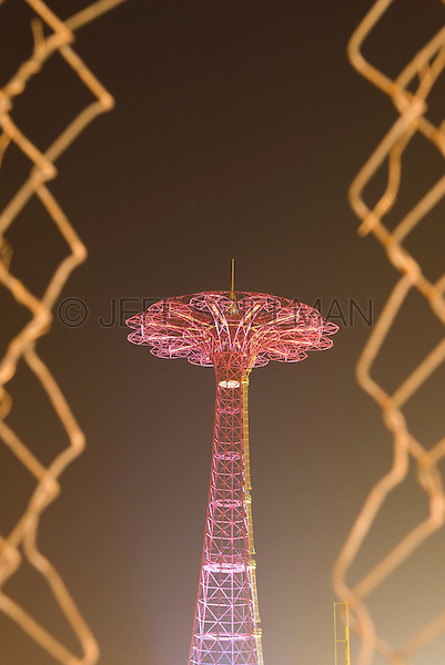 AVAILABLE FROM JEFF AS A FINE ART PRINT.<br /> <br /> AVAILABLE FROM CORBIS FOR COMMERCIAL AND EDITORIAL LICENSING.  Please go to www.corbis.com and search for image # 42-19896995.<br /> <br /> Detail of the abandoned Parachute Jump in Coney Island, Brooklyn, New York City, New York State, USA.  Viewed at night thru chain link fence..... The Parachute Jump was built for the 1939 World's Fair in Flushing Meadows Park, Queens, New York City,  and moved to its current location in Coney Island in 1941.  It is a New York City Landmark and is listed on the National Register of Historic Places.
