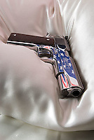 Handgun on pillow with American flag reflected in barrel<br />