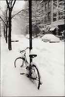 Bicycle chained to a pole in the snow<br />
