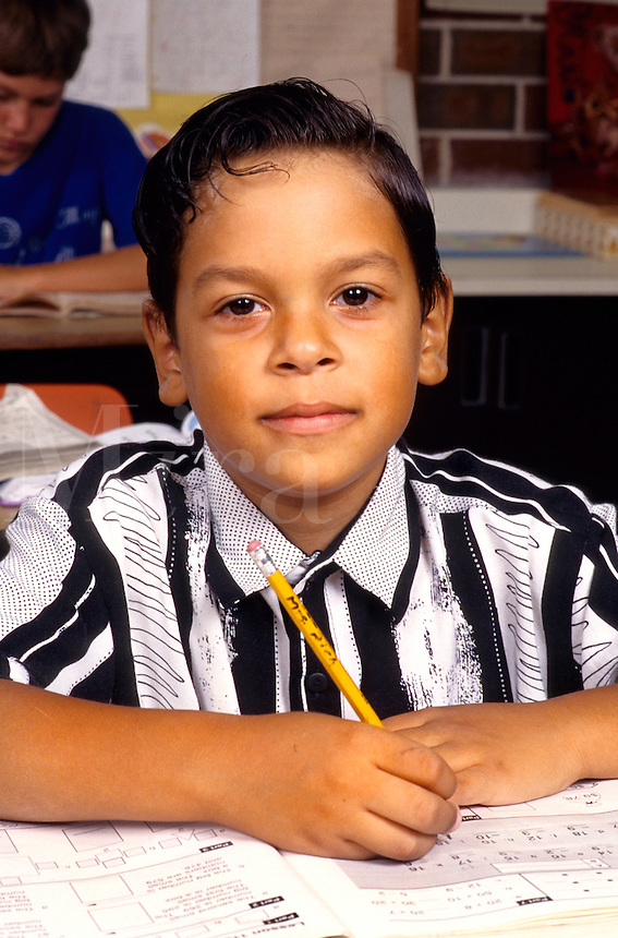 Hispanic Student age 7 working in book on assignment in school portrai