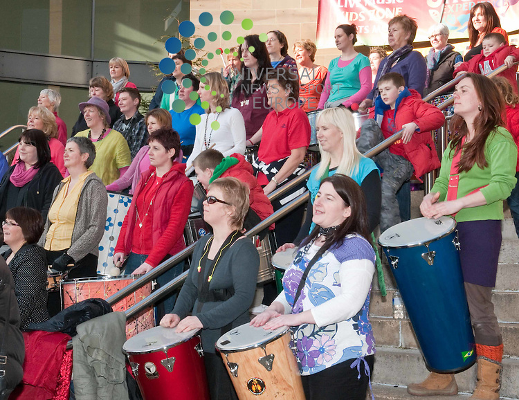 To celebrate the 100th anniversary of International Women's Day 100 women sing and play drums during HUM DRUM to crowds in Buchanan Street Glasgow on 5 March 2011, Picture: Al Goold/Universal News and Sport (Europe) 2011.