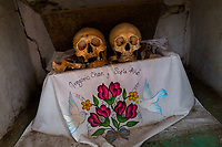 """Dried-up sculls and bones are seen wrapped in a painted cloth and placed in a wooden crate inside a niche at the cemetery in Pomuch, Mexico, 26 October 2019. Every year on the Day of the Dead, people of Pomuch, a small Mayan community in the south of Mexico, visit the cemetery to take part in a pre-Hispanic tradition of cleaning of bones of their departed relatives (""""Limpia de huesos""""). People who die in Pomuch are firstly buried for three years in an above-ground tomb then the dried-up bodies are taken out, bones are separated, wrapped in a decorated cloth, put into a wooden crate, and placed on display among flowers for veneration."""