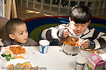 Education Preschool 3-5 year olds lunch time hot lunch two boys eating one overweight pasta with tomato sauce and broccoli horizontal