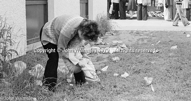 Toddler having a pee, the Education Centre, Festival & Gala Day, Wester Hailes, Scotland, 1979.  John Walmsley was Photographer in Residence at the Education Centre for three weeks in 1979.  The Education Centre was, at the time, Scotland's largest purpose built community High School open all day every day for all ages from primary to adults.  The town of Wester Hailes, a few miles to the south west of Edinburgh, was built in the early 1970s mostly of blocks of flats and high rises.