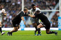 Billy Vunipola of England is tackled by Tony Woodcock (right) and Owen Franks of New Zealand during the QBE Autumn International match between England and New Zealand at Twickenham on Saturday 16th November 2013 (Photo by Rob Munro)