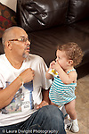 13 month old baby girl at home with father who is her primary caregiver talking about and playing with nesting stacking boxes vertical
