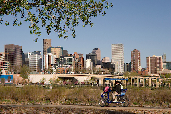 Hispanic family biking in Confluence Park near downtown Denver, Colorado. .  John offers private photo tours in Denver, Boulder and throughout Colorado. Year-round.