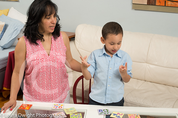 3 year old boy playing memory game with mother, counting on his fingers