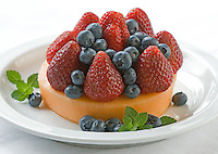 Strawberry, blueberry and cantaloupe fruit plate with mint sprig on white plate with white table cloth.