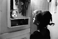 """USA. New York City. Spanish Harlem. Sala looks at herself in the mirror in the bathroom. The Puerto Rican family lives below the poverty line and receives public assistance (AFDC, Home Relief, Supplemental Security Income and Medicaid). The family resides in units managed by the New York City Housing Authority (NYCHA) which provides housing for low income residents. NYCHA administers rental apartments in facilities, popularly known as """"projects"""". Spanish Harlem, also known as El Barrio and East Harlem, is a low income neighborhood in Harlem area. Spanish Harlem is one of the largest predominantly Latino communities in New York City. 4.04.86 © 1986 Didier Ruef"""
