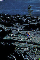 Young woman running on the black lava fields at Volcanoes National Park on the Big Island