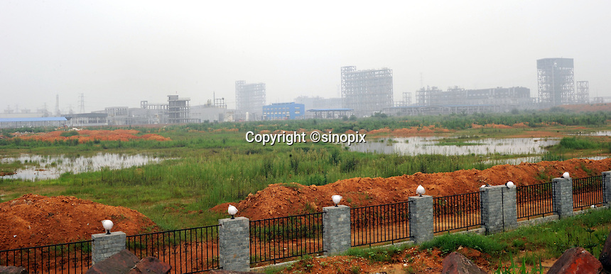 Renesola polysilicon plant in Meishan Sichuan, China. Almost a thousand villagers in the area that were relocated when Renesola bought their land for planned expansion and were not adequately compensated. Many now live in a squatter village next to the plant.<br /> <br /> photo by Richard Jones/Sinopix
