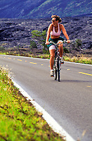 A fit looking woman rides a bicycle on a road in Hawaii Volcanoes National Park on the Big Island.