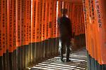 Blurred figure walks through Torii gates, Fushimi Inari Shrine, Kyoto, Honshu, Japan , Fushimi Inari-taisha