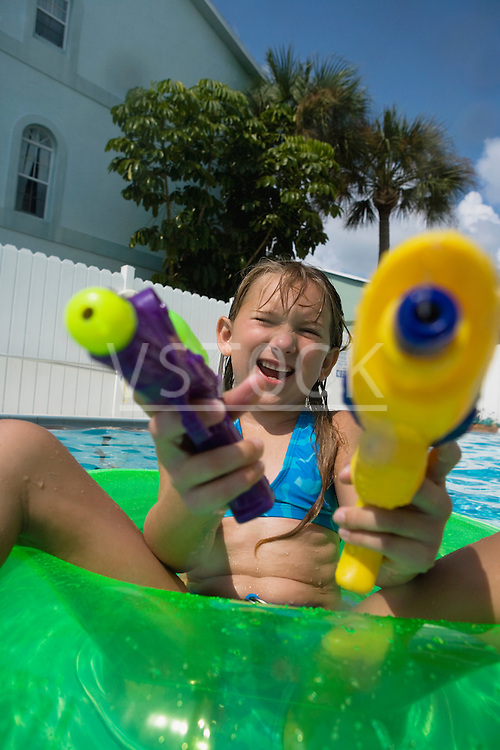 Young girl (6-8) playing with toy guns in swimming pool