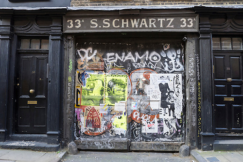 33 to 35 Fournier Street, Spitalfields, London. Georgian tradesman's double door yard entrance flanked by two typical period front doors with rectangular fanlights. Signwriting over the entrance says '33A S. SCHWARTZ'. Graffiti and posters on the doors.