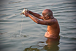 Indian man bathing and making offerings at the Ganges River in Varanasi, Uttar Pradesh, India