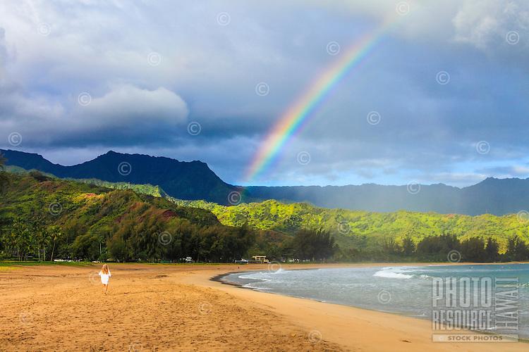 A woman at Kaua'i's Hanalei Beach walks towards a rainbow.