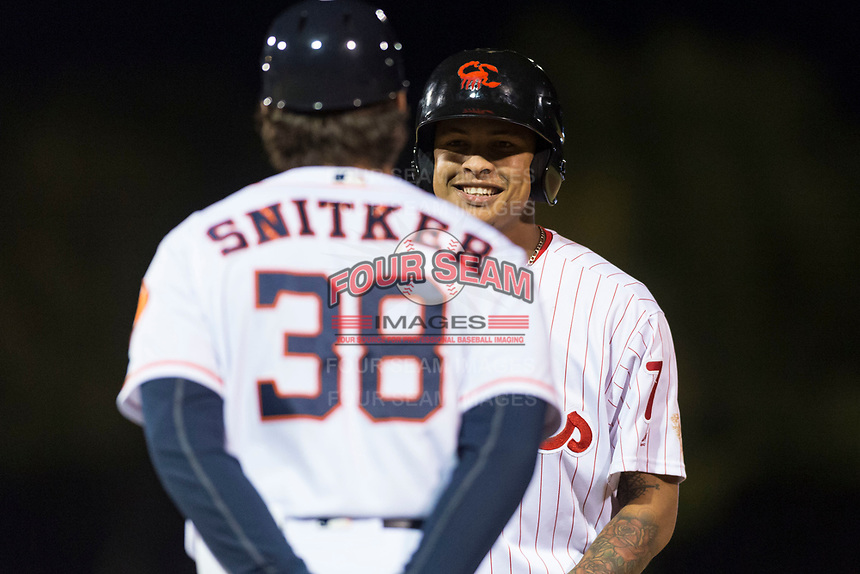 Scottsdale Scorpions shortstop Arquimedes Gamboa (7), of the Philadelphia Phillies organization, laughs with hitting coach Troy Snitker (38) after reaching first base during an Arizona Fall League game against the Surprise Saguaros at Scottsdale Stadium on October 15, 2018 in Scottsdale, Arizona. Surprise defeated Scottsdale 2-0. (Zachary Lucy/Four Seam Images)