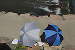 People under umbrellas  along sidewalk and stream, Denver, Colorado, USA.