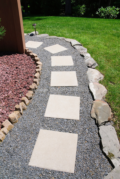 Garden path, simple stones set into gravel, edged with stones, near lush green lawn grass, curving, next to red stone mulched bed, backyard