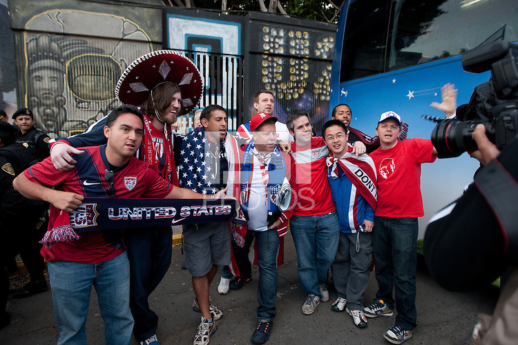 USA fans have their photo taken by a photographer.  Mexican police officers in riot gear formed a perimeter around a bus of USA fans arriving for the USA vs. Mexico World Cup Qualifier at Azteca stadium in Mexico City, Mexico on March 26, 2013.