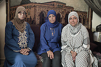 Posing in front of El Aqsa Three generation of palestinans women, the grand mother the mother and the daughter. The latter now lives in Norway where she studies. Behind them on the wall an artcraft of the first mosque before the dome rock in jerusalem, El Aqsa Mosque, which they consider sacred and legitimate. The dome of the rock was built after by the Israelis. Beirut, Lebanon. August 2015