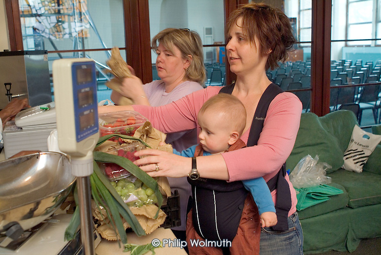 Mother and baby at community food co-op at  Westbourne Park Family Centre, West London.