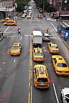 A street view looking at yellow cabs from the High Line which is a public park built on a 1.45-mile-long elevated rail structure running from Gansevoort Street to West 34th Street on Manhattan's West Side, New York City.
