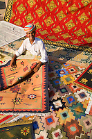 Rug designer Roopraj Prajapati shows off his hand-made carpets in village outside Jodhpur, Rajasthan, India