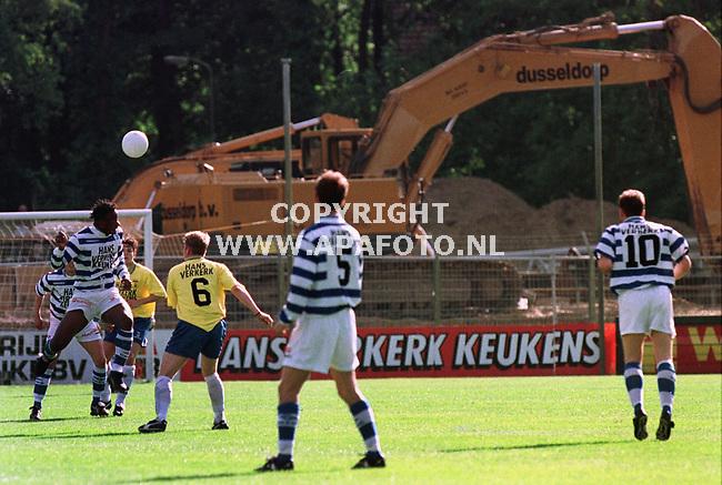 Doetinchem,22-05-99  Foto:Koos Groenewold (APA)<br /><br />Vrijblijvend voor COBOUW<br /><br />De provincie Gelderland telt 3 ere-divisie voetbalclubs  te weten:Vitesse,NEC en De Graafschap.<br />Vitesse heeft in 1998 een splinternieuw stadion in gebruik genomen en momenteel zijn de andere 2 Gelderse clubs druk bezig met een totale renovatie van hun onderkomens.NEC uit Nijmegen sloopt momenteel alle oude tribunes en zet er splinternieuwe voor in de plaats.De Achterhoekers van De Graafschap wilden natuurlijk niet achterblijven en de deden vorig jaar aan het eind van het voetbalseizoen hetzelfde: 2 tribunes werden afgebroken en er werden nieuwe neergezet.Onlangs is begonnen met de sloop van 1 van de 2 overgebleven tribunes .Op de achtergrond is een grote bulldozer te zien,terwijl De Graafschap zijn laatse competitiewedstrijd afwerkte tegen de Friezen van Cambuur.(uitslag 2-2)<br />Als het goed is zal De Graafschap volgens seizoen in een totaal gerenoveerd stadion spelen,met alleen nog maar zitplaatsen en zonder hekken rondom het veld.