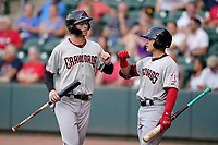 First baseman Jake Guenther (15) of the Hickory Crawdads is greeted by David Garcia (13) after scoring a run in a game against the Greenville Drive on Friday, June 18, 2021, at Fluor Field at the West End in Greenville, South Carolina. (Tom Priddy/Four Seam Images)