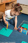 Education Preschool girl, age 3, making tower of stacking colorful plastic pegs