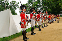Soldiers of the 16th Light Dragoons and His Majesty's 4th and 10th  Regiments of Foot prepare for battle at a Revolutionary War encampment, Old Sturbridge Village, Massachusetts, USA.