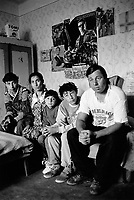 Hungary. Baranya county. Nagybajom is a gypsie village.  Family portrait. The mother, father and three children are seated on a couch in their living room. On the wall, a poster from the film Terminator 2 starring Arnold Schwarzenegger. Terminator 2: Judgment Day (also promoted as T2) is a 1991 American science fiction action film produced and directed by James Cameron. The boy (second right) is a pupil from Gandhi High School come from the village. The purpose of the middle school / high school is to provide a school-leaving exam (A-level), also to improve the prospects of Romani children in Hungary and to help preserving the Romani culture. The Romani people, also known as the Roma, are an Indo-Aryan people group, traditionally nomadic itinerants living mostly in Europe. The Romani people are widely known in English by the exonym Gypsies (or Gipsies), which is considered by many Romani people to be pejorative due to its connotations of illegality and irregularity as well as its historical use as a racial slur. In many other languages, they are called Roms (Rroms), Tziganes,Tsiganes, Gitans, Bohémiens, Manouches, Romanichels, gitano, zingaro and cigano. 13.05.95 © 1995 Didier Ruef