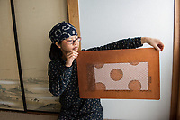 Japan, Mie Prefecture, Suzuka city. The art of stencil. Yoshinori Ikuta, 69, is a master stencil artist and his female student Keiko Nasu, 33, has been working closely with him for five years. These stencils, cut by hand, are used for unique kimono and scarf patterns and can take up to a month for each design. This is generally a male oriented profession, he learned from his father and wanted to continue the business but now not so many are wearing kimonos. Keiko loves kimonos and patterns, cutting paper, it requires concentration and stability. She makes six copies at a time and sells the original. With Keiko as a student Mr. Ikutu realizes how much he learned so the student became the teacher. They both feel a responsibility for continuing this dying tradition. Model released